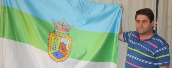 Un vecino muestra la bandera y el escudo de Montecorto. // CharryTV
