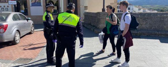 Dos agentes de la Policía Local piden a dos transeúntes que justifiquen su salida. // CharryTV