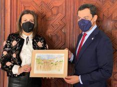 La alcaldesa de Ronda ha entregado al presidente de la Junta una lámina del Puente Nuevo, obra de la artista local Lola Lobato // CharryTV